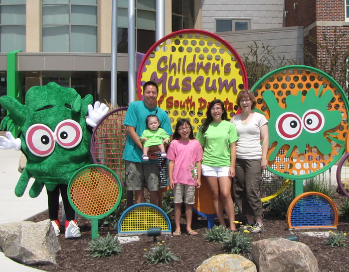 Family of 5 standing in front of CMSD sign with Museum mascot Kidoodle