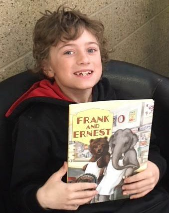 A boy holding up the book, Frank and Ernest.