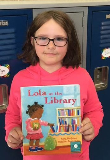 A girl holding up the book, Lola at the Library.