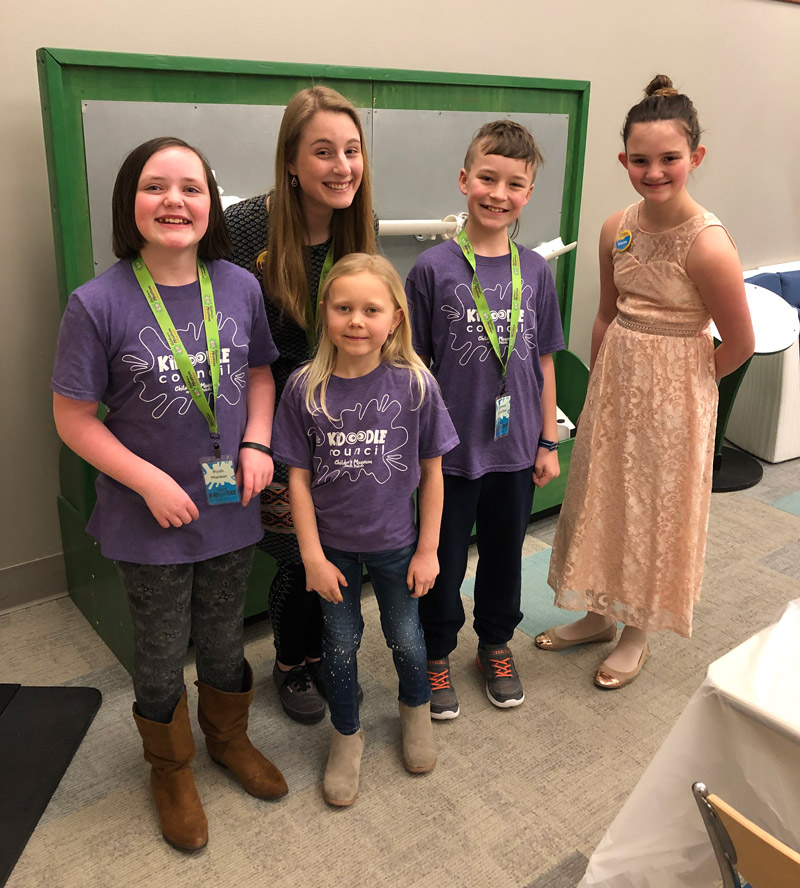 Four children posing with a staff member during a volunteer opportunity at the children's museum