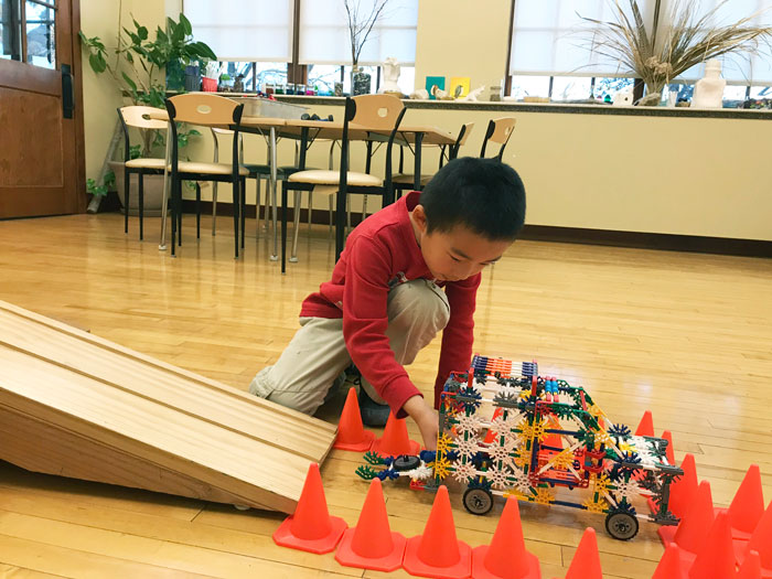 Boy playing with constructed car on a ramp in the Maker Studio.