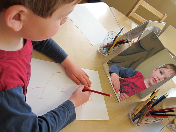 Boy looking at himself in mirror drawing self portrait with colored pencils.