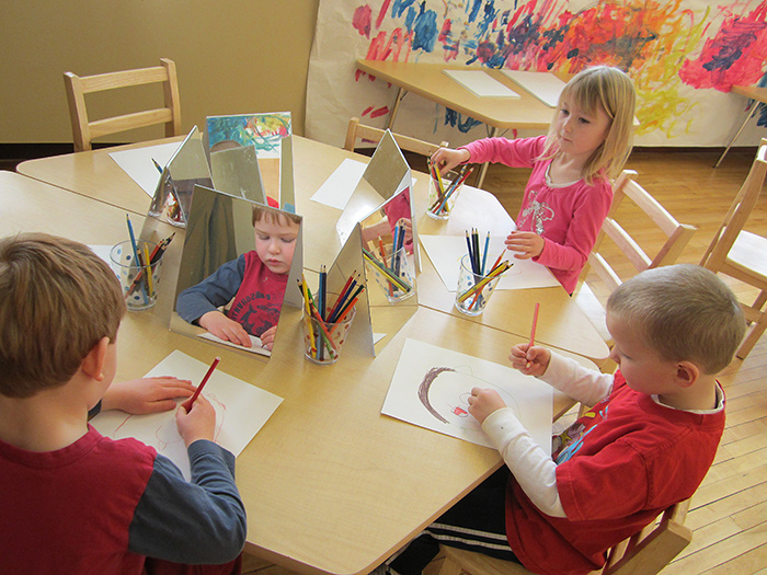 Three children at table each with a mirror to draw a self-portrait in the Maker Studio.