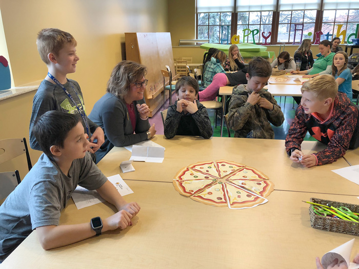 Five boys at table with female teacher discussing pizza culture activity.