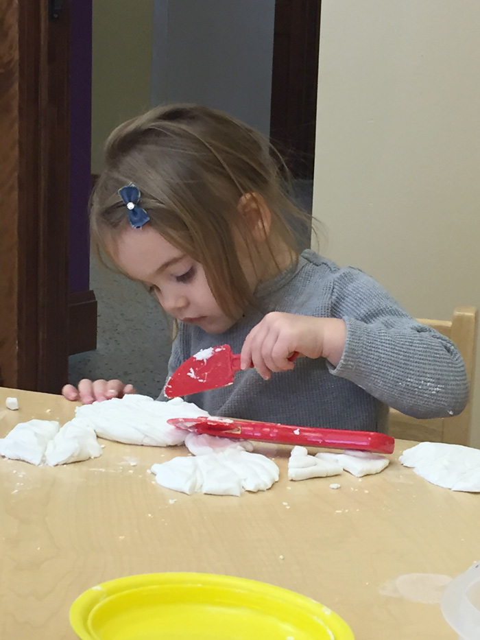 Toddler sitting at table exploring dream dough in Maker Studio.