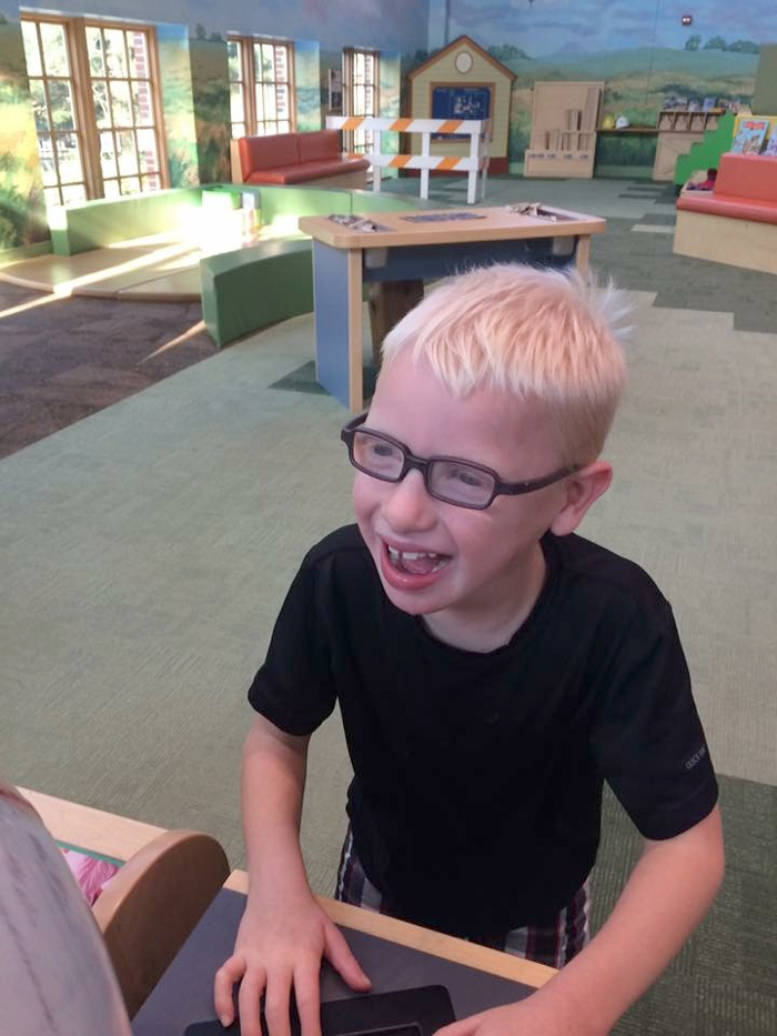 Boy with glasses smiling and playing at an exhibit in Children's Museum.
