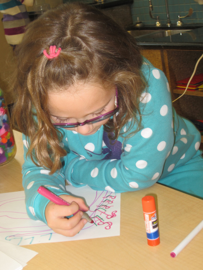 Young girl drawing with marker at a table in the maker studio.