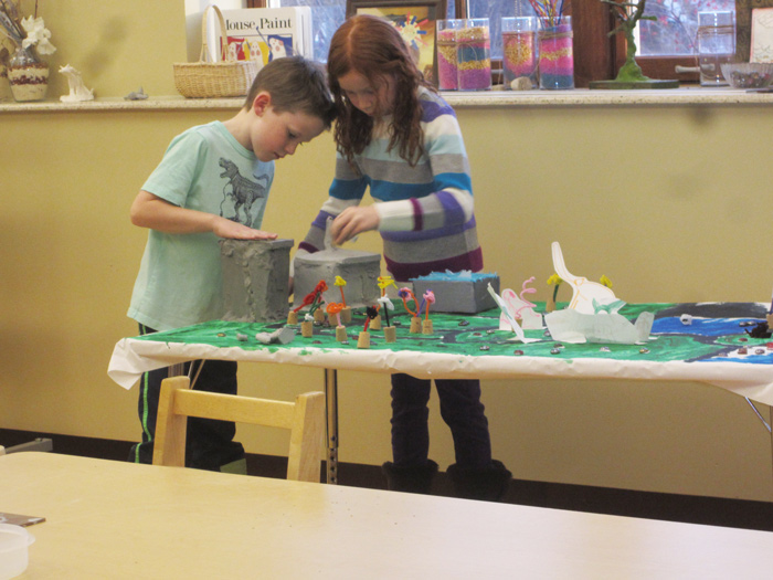Two children working together to create clay sculpture of a building.