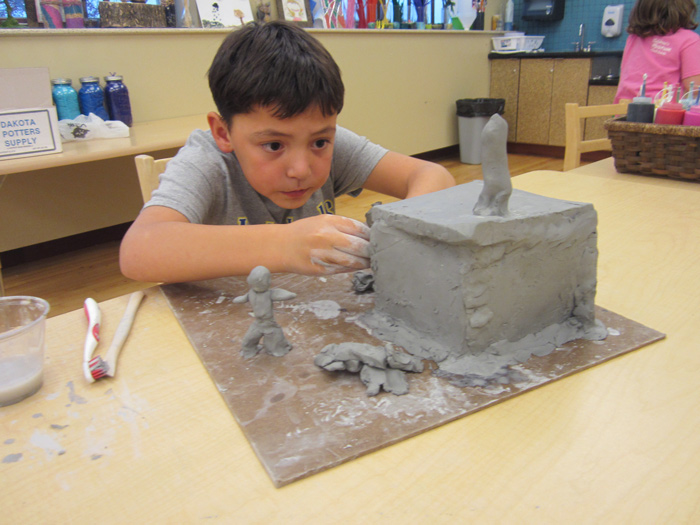 Boy sitting at table creating clay house during maker studio class.