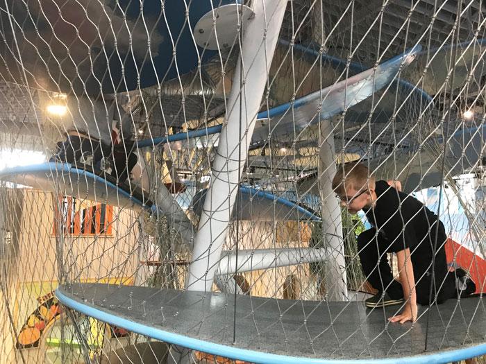 Boy climbing two-story high cloud sculpture on children's museum prairie.