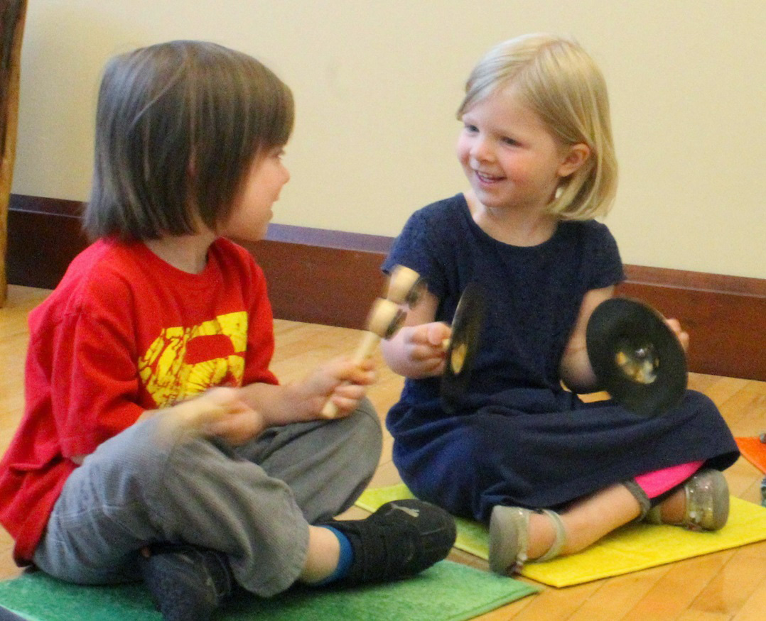 Two children sitting on floor playing instruments smiling at each other.