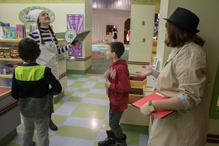 Two characters giving clues to two boys at the Children's Museum Mystery Dinner Theater event.