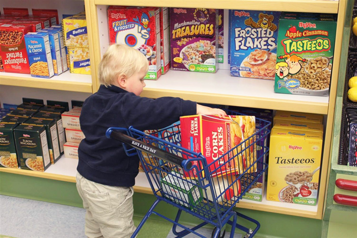 Boy filling miniature grocery cart with box of cereal at Children's Museum.