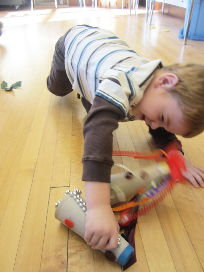 Action shot of boy crawling on floor with craft sculpture.