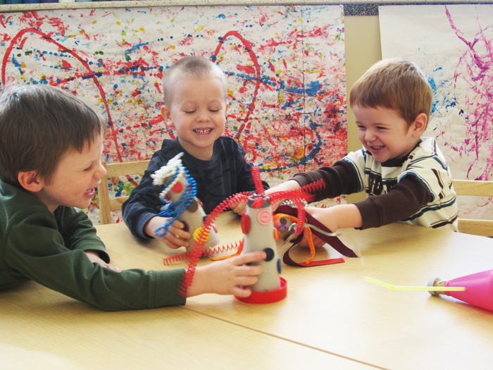 Three boys laughing with craft sculptures around table.