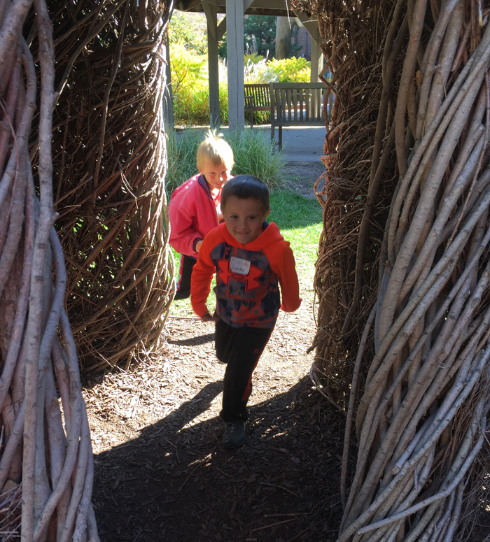 Two boys running through Patrick Dougherty's Tangle Town sculpture at the Children's Museum of South Dakota.