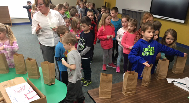 Class of children standing in line to place vote in paper bag.