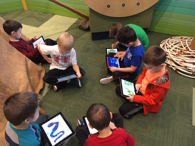 Five children sitting on floor documenting learning on ipads.