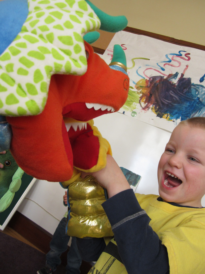 Boy laughing at puppet dragon.