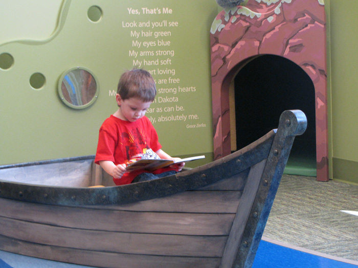 Young boy reading book in play boat in a children's museum exhibit.