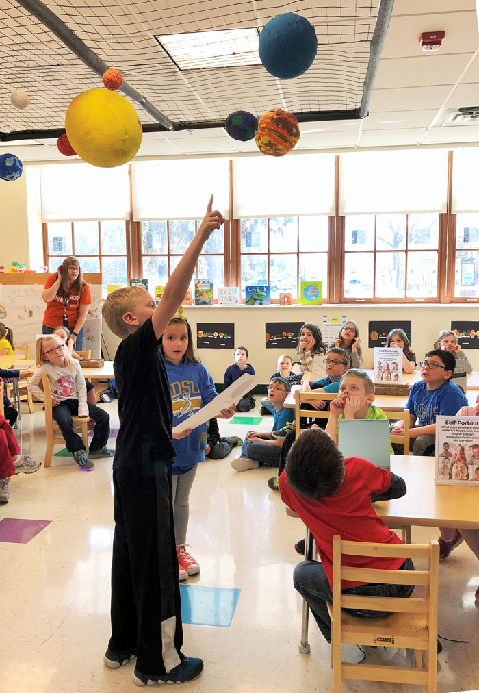 Child pointing at planet sculptures hanging from ceiling in the art studio while class sitting in chairs looks on.