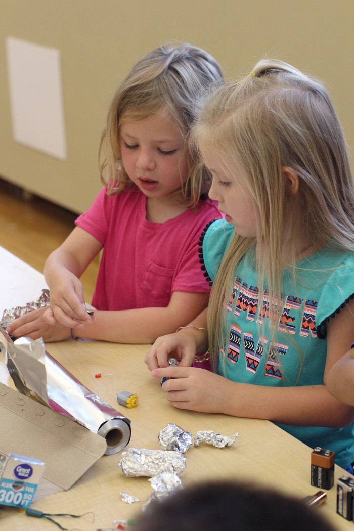 Two girls exploring aluminum foil circuits at a table in the Maker Studio.