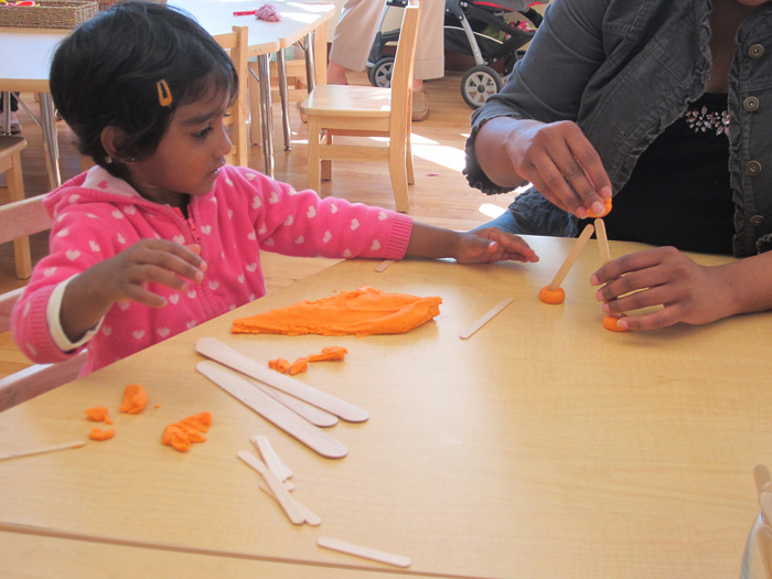 Young girl sitting at table playing with dough in the Maker Studio.