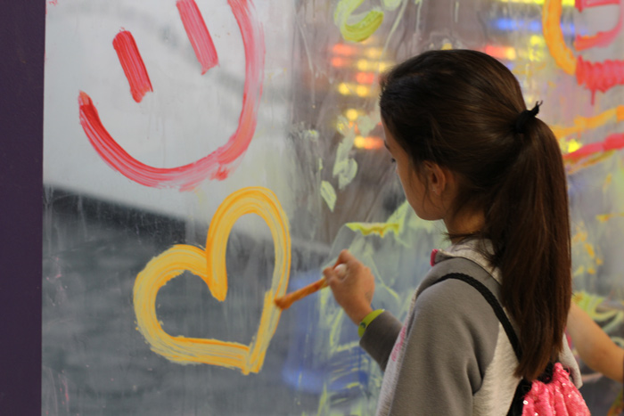 8-year-old child painting on acrylic wall at Children's Museum of South Dakota.