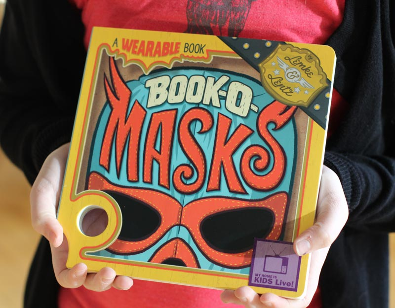 A child's hands holding the book, Book-O-Masks.
