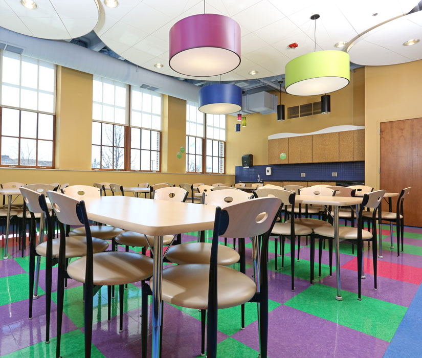 View of Party on 1 rental and classroom space. Colorful floor and wooden tables and chairs.