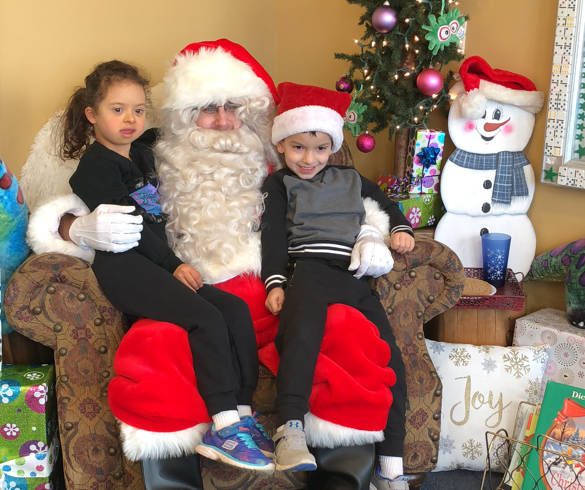 Two children sitting on Santa's lap during a Sensory Friendly Play event at the Children's Museum.
