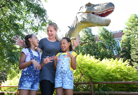 Mom and two girls laughing in front of lifesize animatronic T-rex