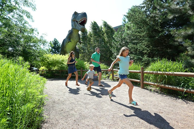 A family of four running by Mama T.Rex at the Children's Museum of South Dakota.