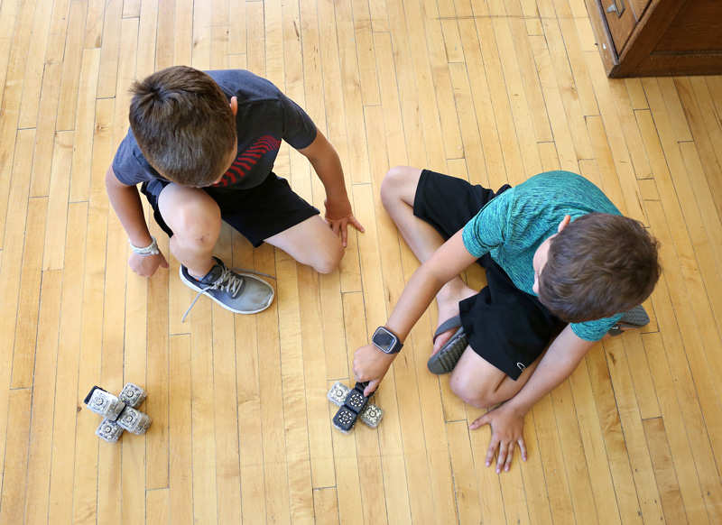 Two boys testing robotic toys on the wooden floor of the maker studio.