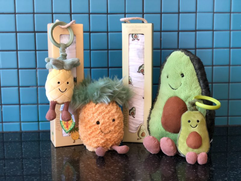 A variety of pineapple and avocado Jellycat baby items.