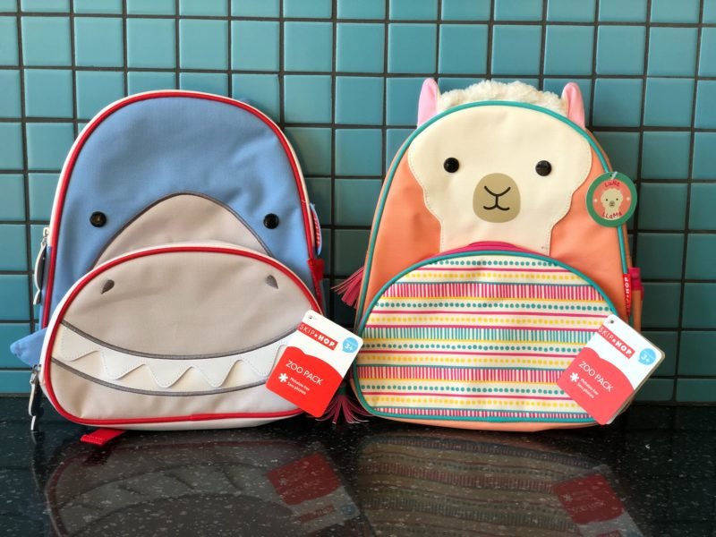 Display of a shark and llama Skip Hop backpack.
