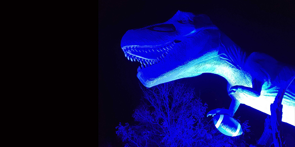 Mama T. Rex holds a giant inflatable football bathed in blue light.