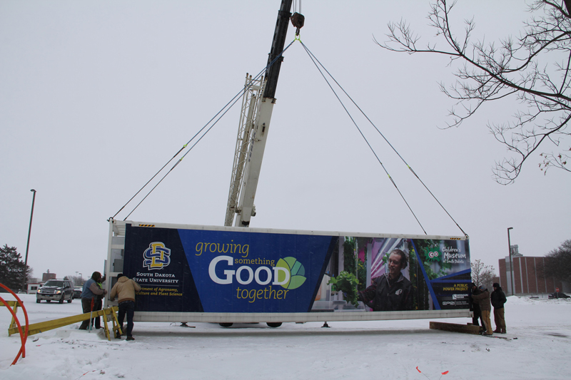 Food pod trailer being set in place by a crane.
