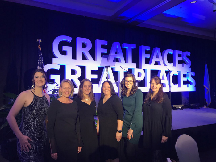 Members of the Brookings, SD tourism community pose in front of the Great Faces Great Places sign