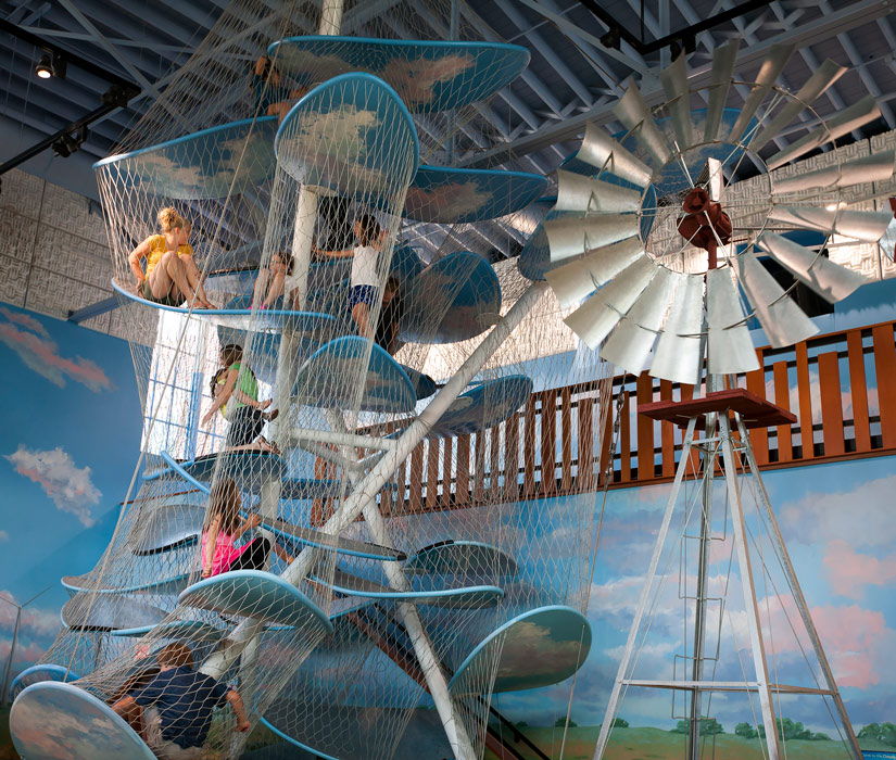 Kids playing in cloud climber with full-size windmill in foreground on museum prairie.