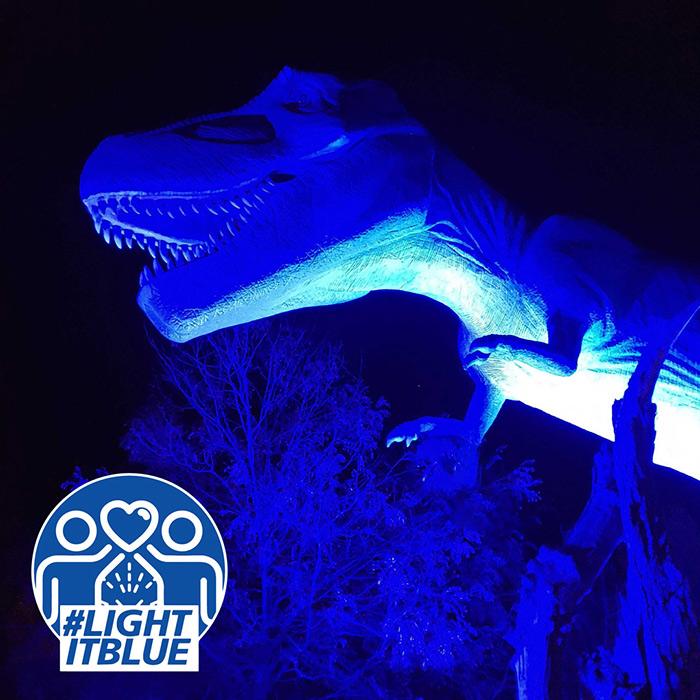T. rex dinosaur bathed in blue light for #lightitblue campaign