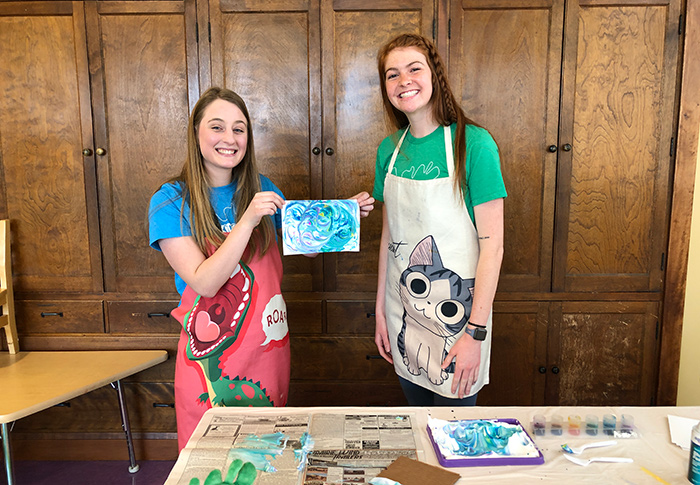 Two women holding up a piece of shaving cream art with supplies on the table in front of them.