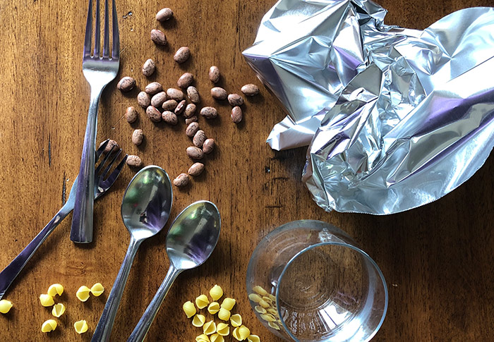 Fork, spoon, foil, pasta, and beans sitting on a table.