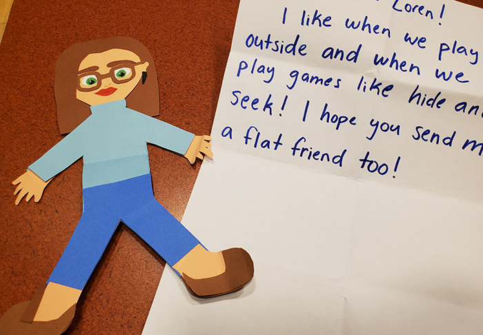 Cut out of a person with glasses next to a hand-written note.
