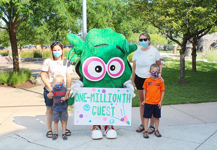 Four people standing with museum mascot Kidoodle holding a one-millionth guest sign