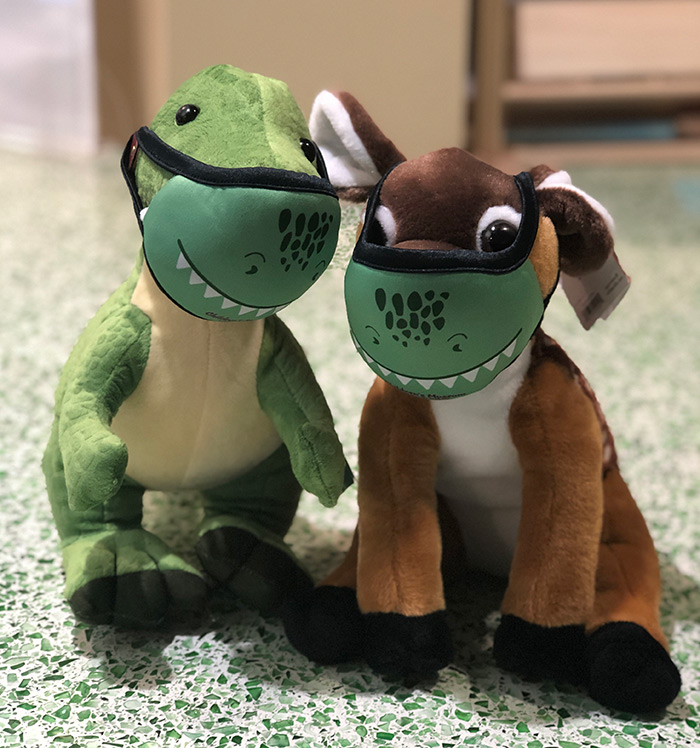 Dinosaur and fawn plush wearing a dinosaur face covering