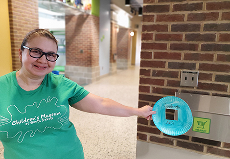 Woman in green shirt smiling and holding up blue plate tool used for scavenger hunt
