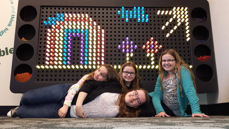 Five girls lying down and smiling near a giant light bright featuring a rainbows, flowers, and sunshine.