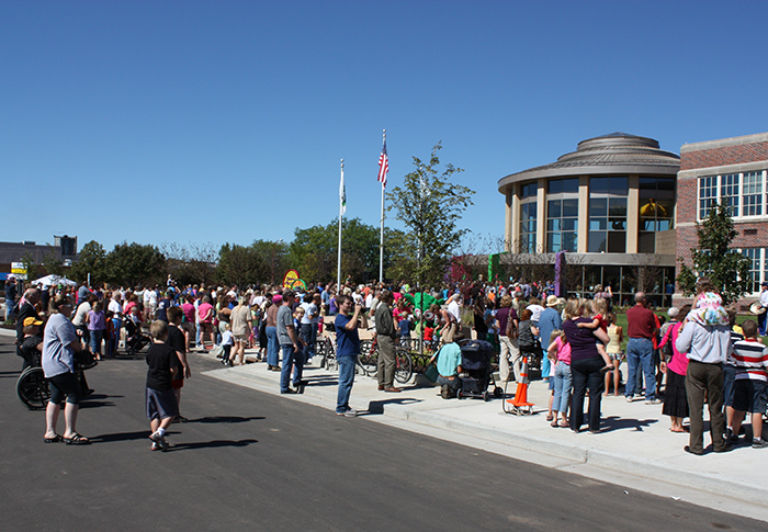 Crowd of people standing outside on lawn during Museum's grand opening celebration.