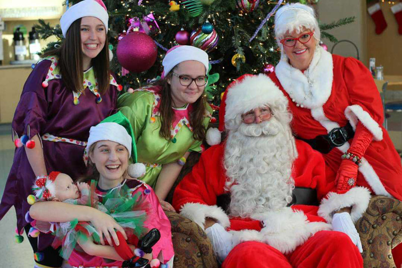 Santa and Mrs. Claus in front of Christmas tree smiling with three elves, one of whom is holding an infant.